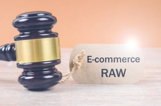 E-commerce law tag and Wooden judge gavel. E-commerce law.