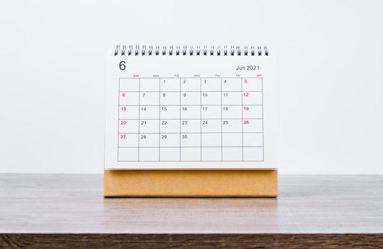 June Calendar 2021 on wooden table.