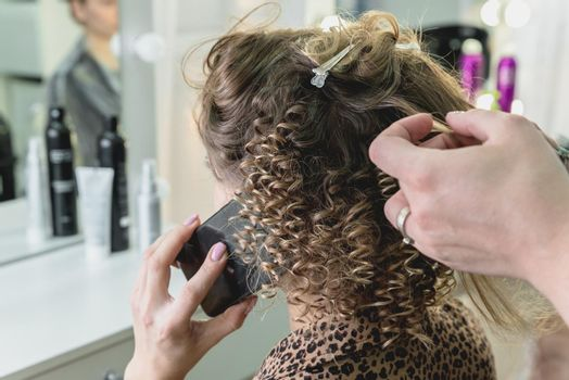 Woman in beauty salon doing hairdo and talking by mobile phone