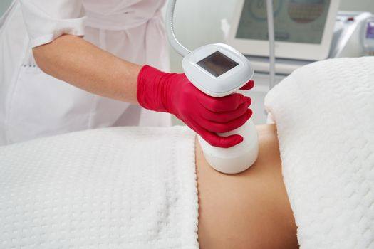 professional cosmetologist performing radiofrequency lifting procedure on the stomach of a woman