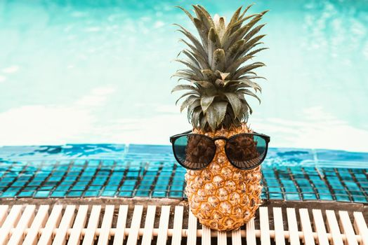 Summer Vacation and Swimming Pool Relaxation Lifestyles Concept, Pineapple With Sunglasses in Poolside at The Beach Vacations. Tropical Leisure Activities Relaxing and Holiday Resort