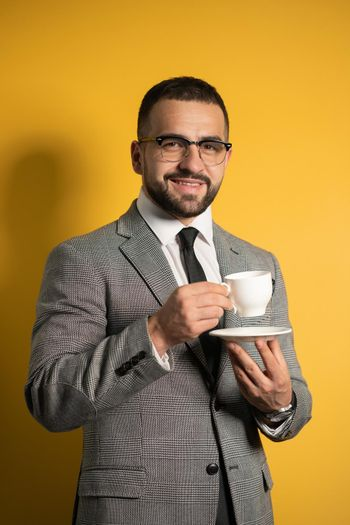 Handsome bearded young man in eye glasses in formal wear holding a cup of coffee isolated on yellow background. Business, hot drinks and people concept