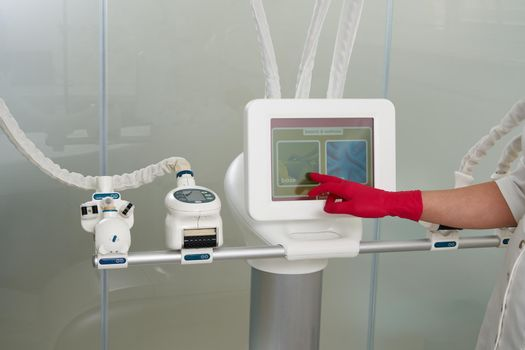 Cropped view of cosmetologist operating modern cosmetology equipment beauty clinic. Modern beauty medical clinic concept