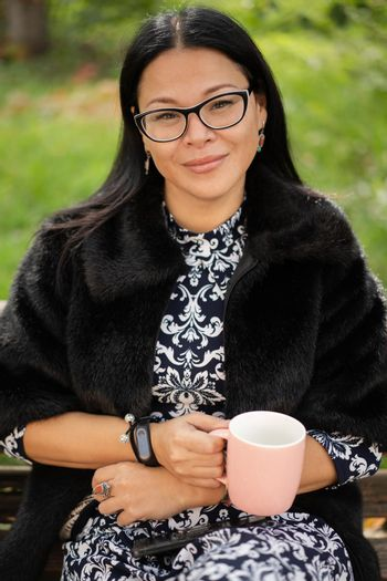 Close up charming asian woman in fur coat and beautiful dress sits at park on old rusty bench with a pinkish cup of coffee or tea. Resting woman in sunny day outdoors