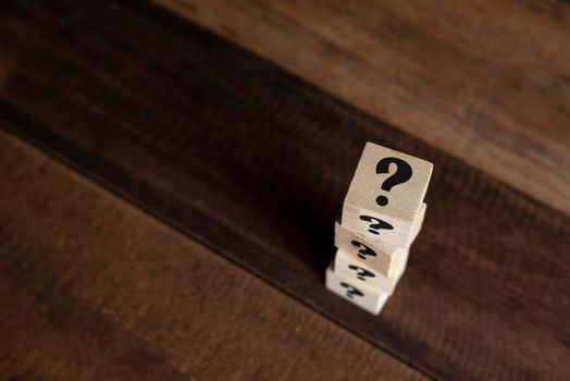 Stacked wooden cube with question mark on table.