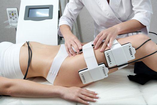 Beautiful woman getting electro stimulation therapy. Laser lipo equipment. Cosmetic fat reduce treatment. Anti cellulite procedure