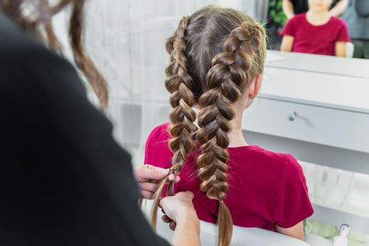 Hairdresser weaves a braid to a preteen blond girl in a beauty and hair salon