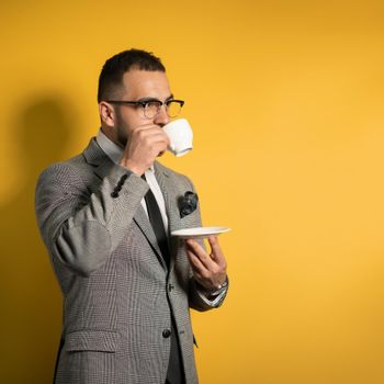Handsome young bearded business man in eye glasses in formal wear holding a cup of coffee standing sideways isolated on yellow background