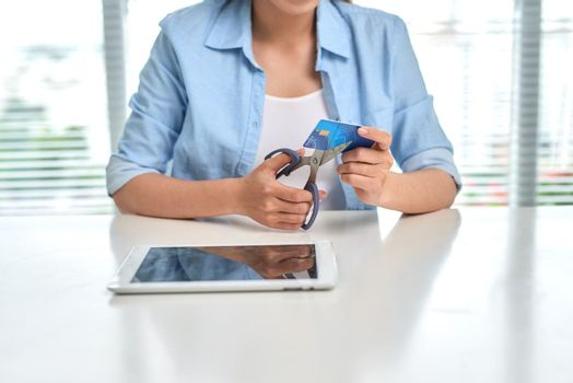 Female shopaholic cutting her credit card with scissors