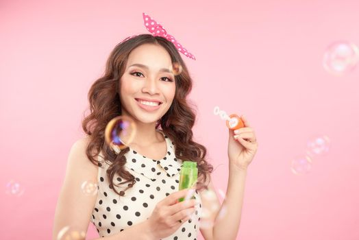 Playful woman blowing party bubbles at the camera as she celebrates a special occasion or birthday, over pink background
