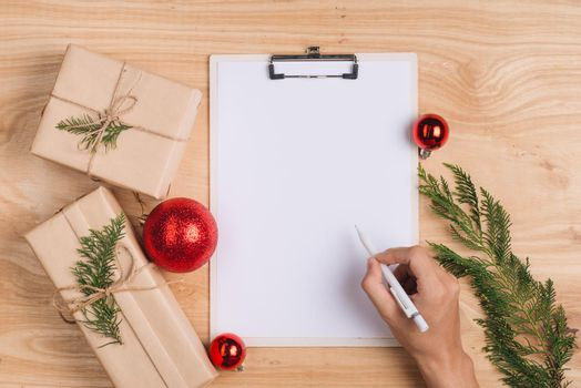 Male writing xmas greeting card and wrapping christmas gifts. Top view with copy space