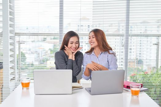 Happy young businesswoman talking to her colleague