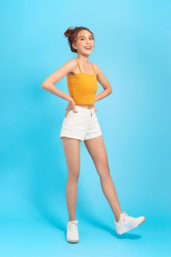 Full-length photo of long-legged girl in white shorts and cropped top on a blue background