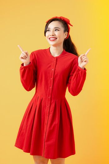 Happy beautiful young woman pointing fingers two sides over orange background.