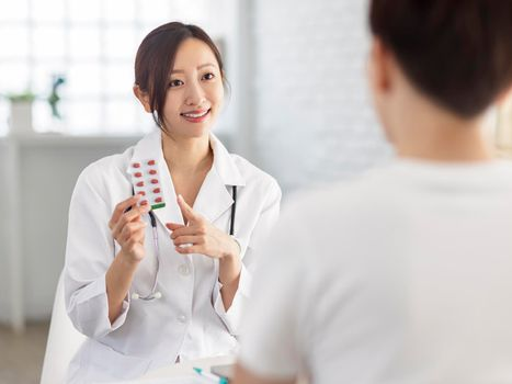 Doctor is pointing to drug tablet and introducing to patient.