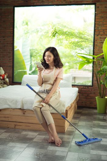 Housekeeping concept. Woman texting while doing housework
