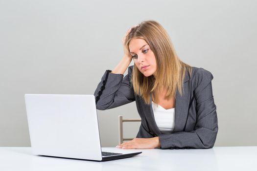Despair businesswoman looking at her laptop