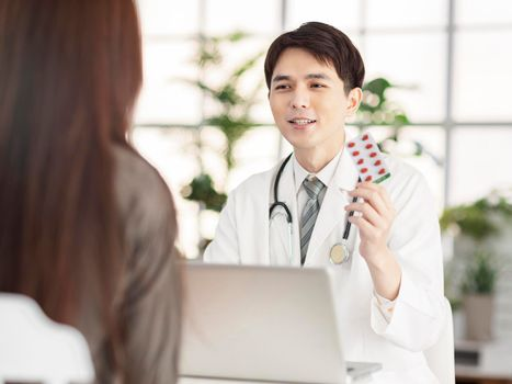 Doctor showing with pills to patient.