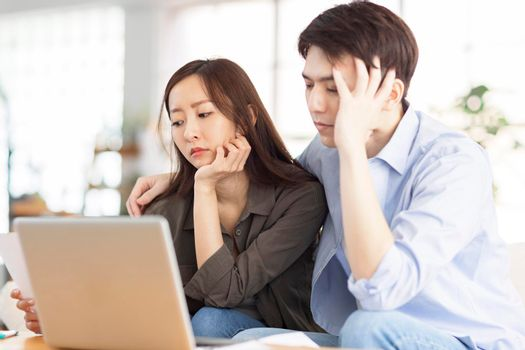 Upset couple using laptop at home.