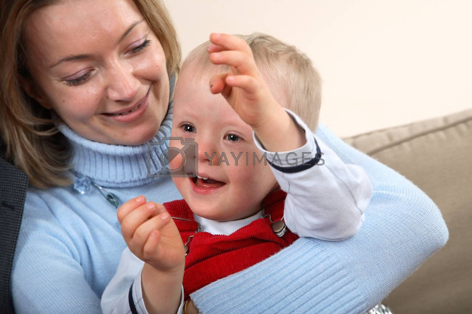 A closeup portrait view of a young boy with Down Syndrome and his mother.