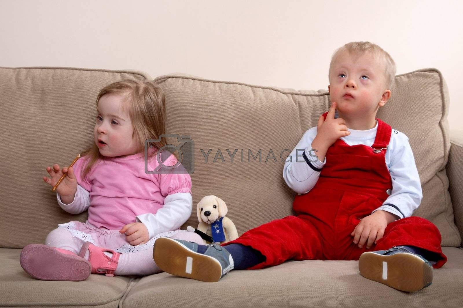 A little boy and girl with Down syndrome sitting on a sofa