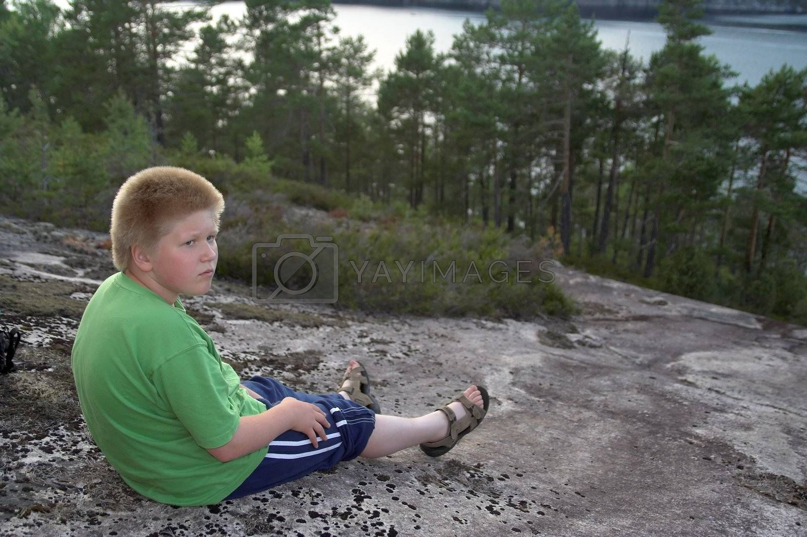 blond boy sitting on the rock above trees and a lake