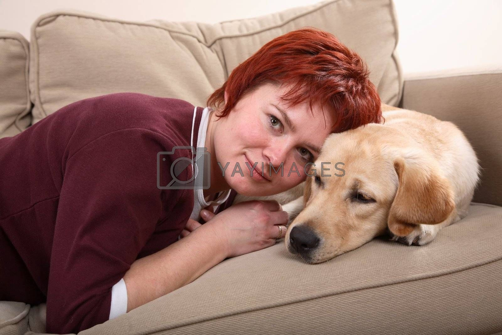 A caucasian woman and her Labrador dog snuggling up on the sofa