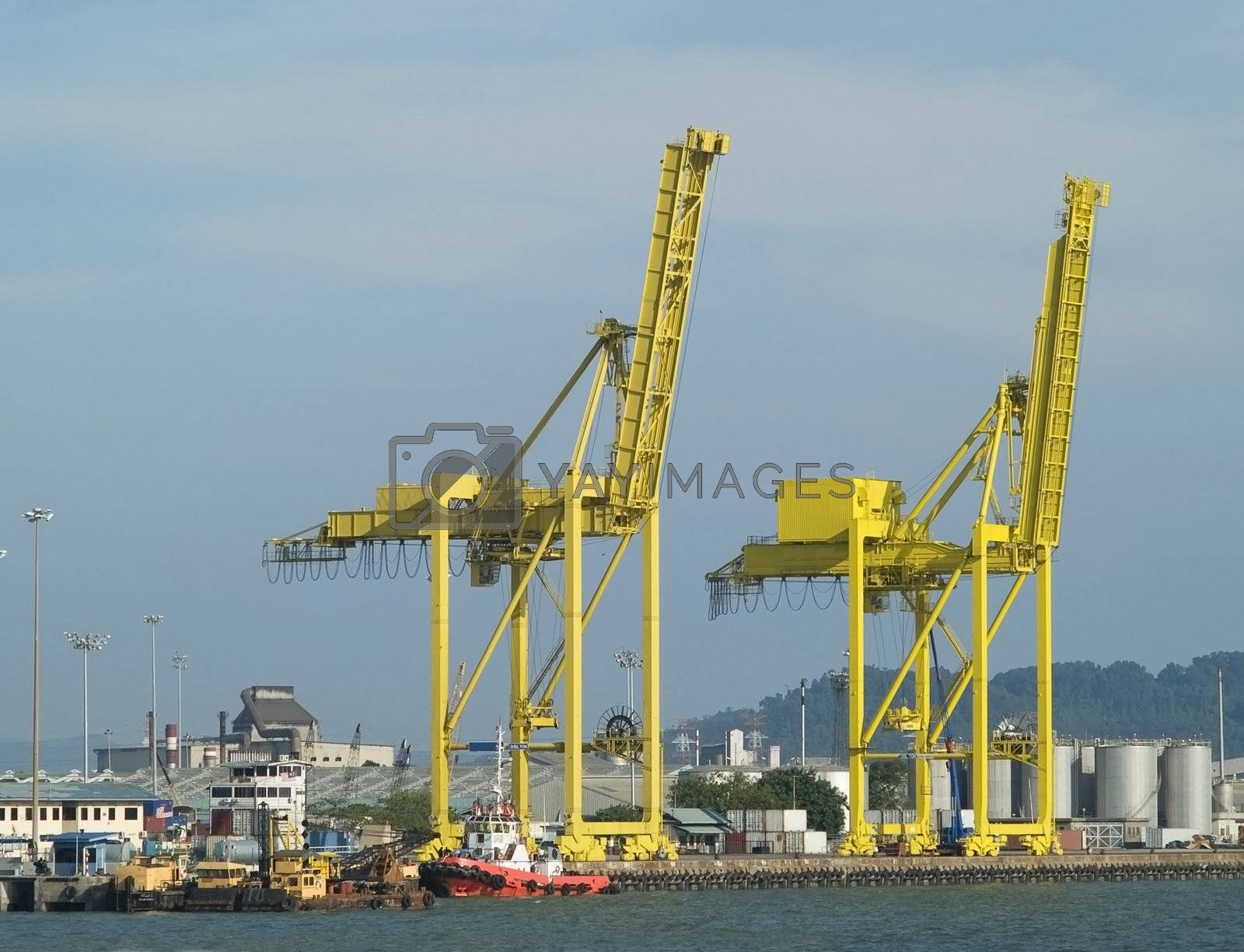 Two container cranes in a harbour by epixx