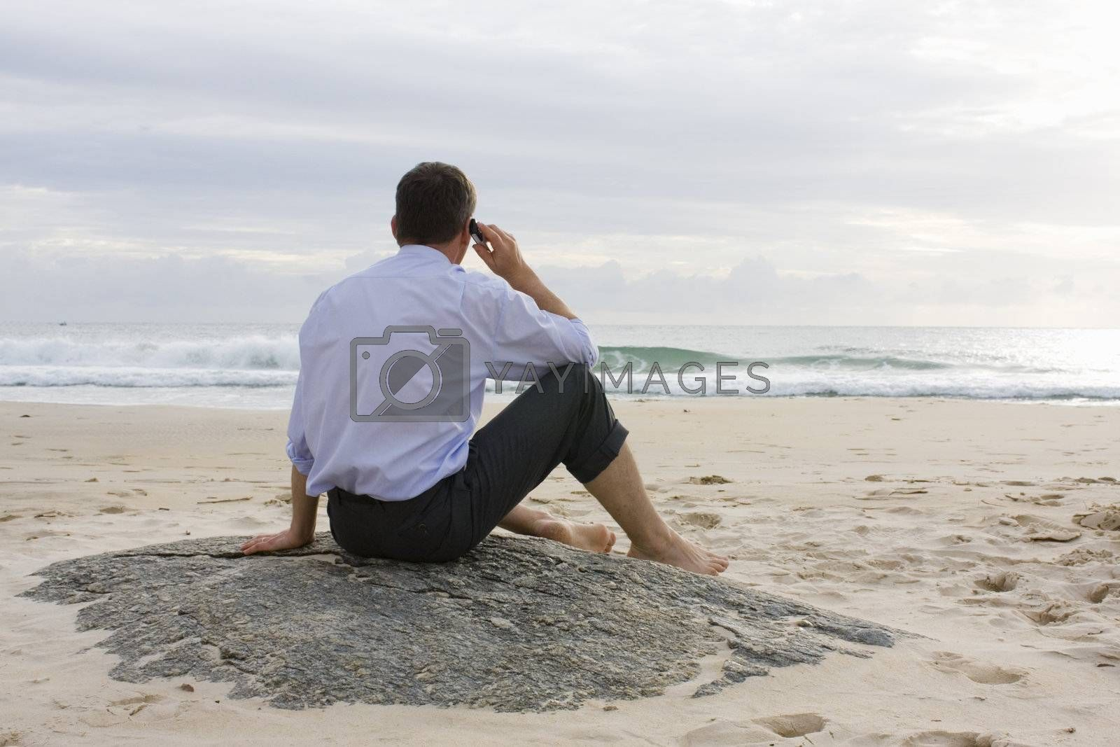Businessman talking on cell phone while sitting on a beach