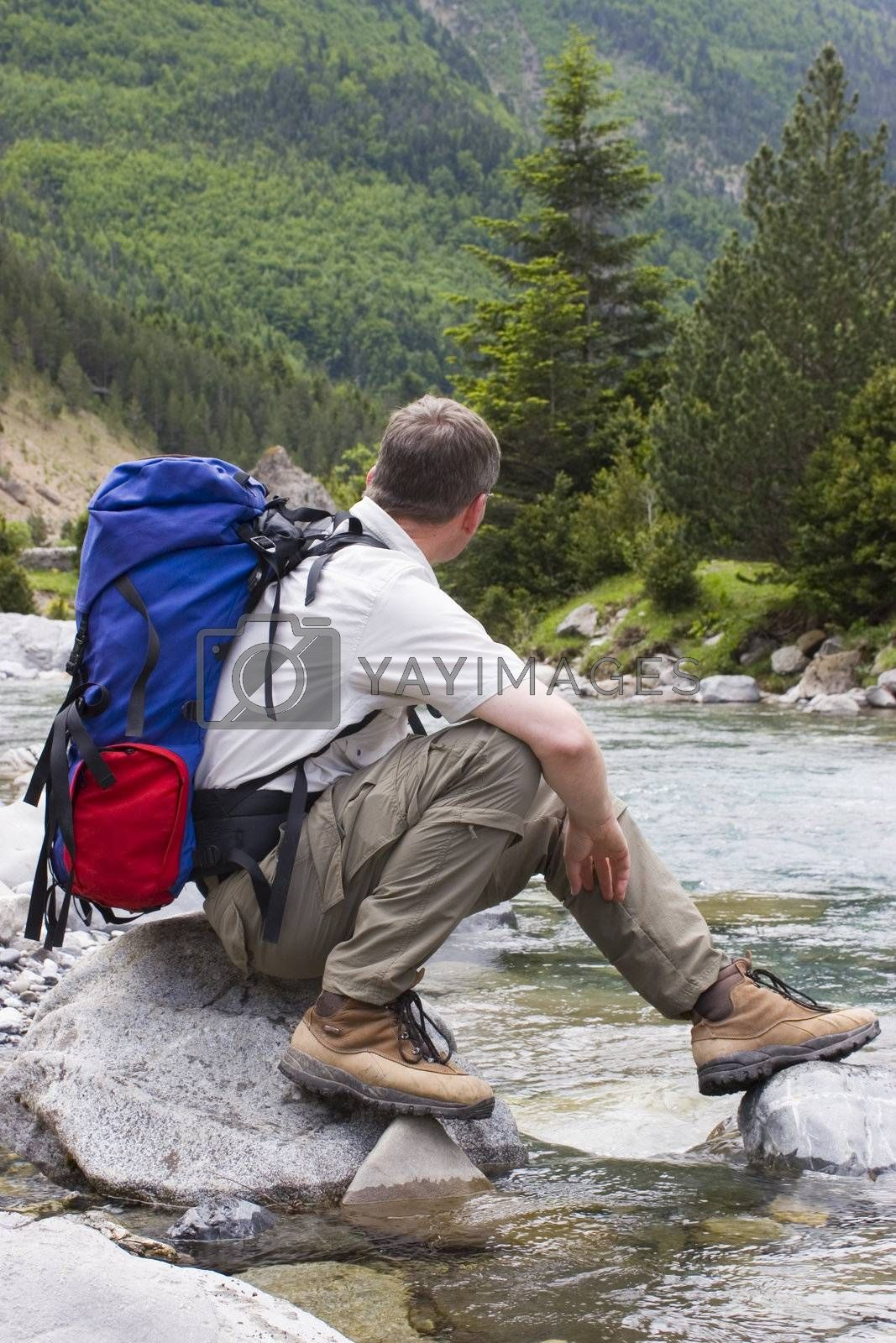 Hiker with backpack resting at a mountain creek. National park Ordesa y Monte perdido - Spain