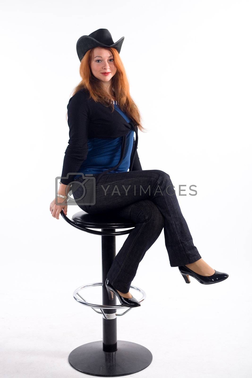 Young girl with  black hat sitting on chair on white background