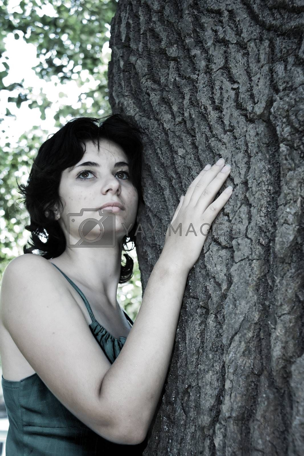 The beautiful girl has embraced a tree