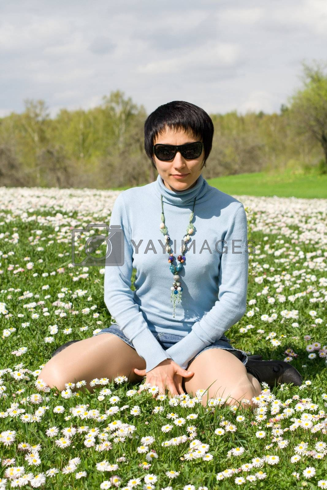 Young sexy lovely woman in sunglasses is posing on the flowering meadow