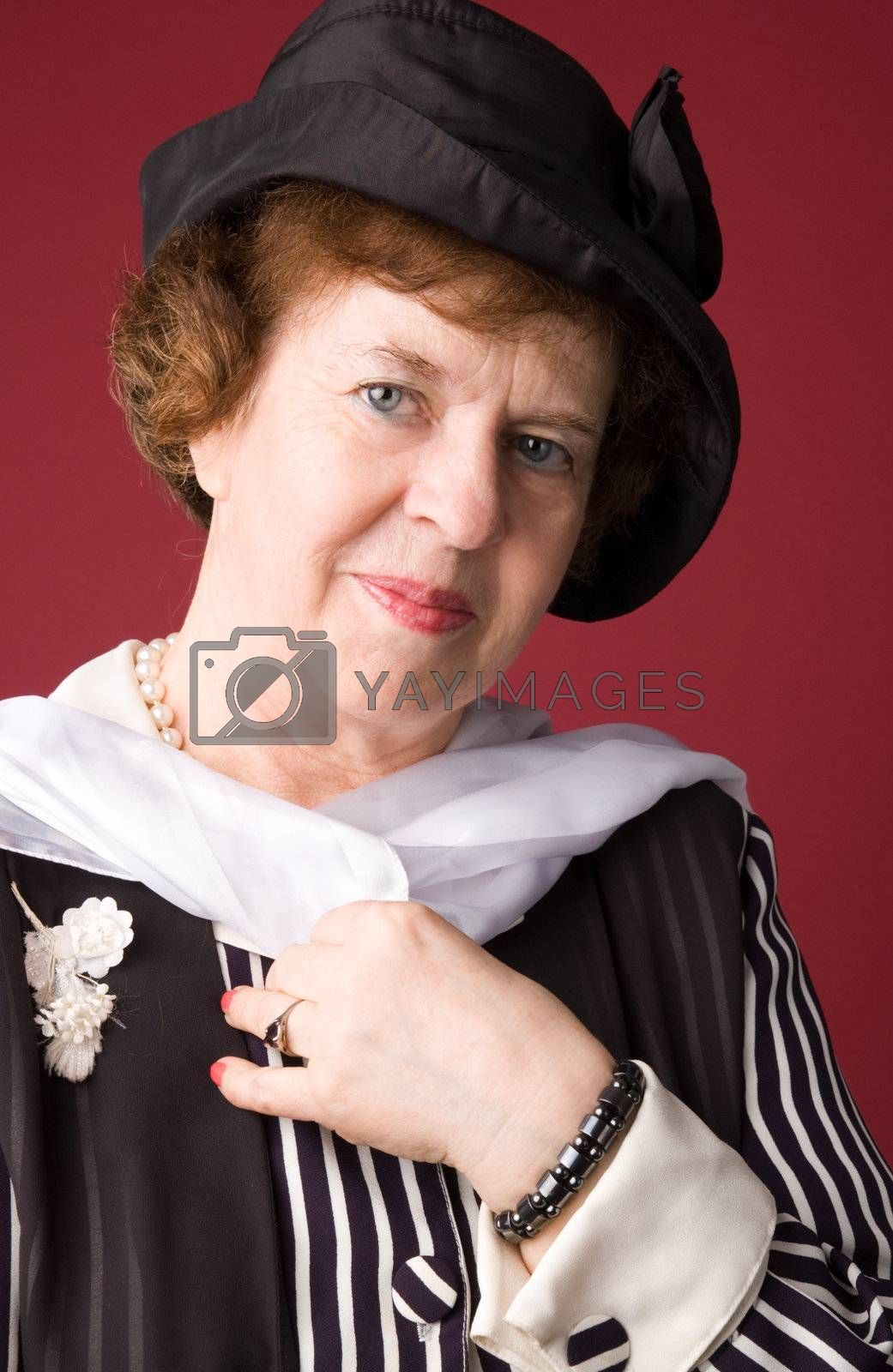 The elderly woman in a hat on a red background.