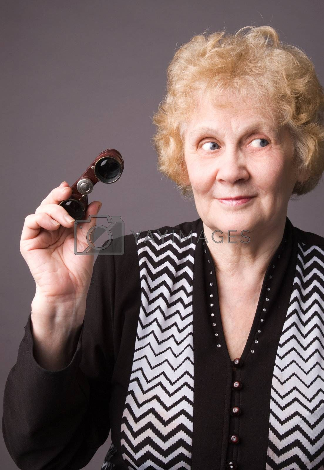 The cheerful elderly woman with binocular on a grey background.