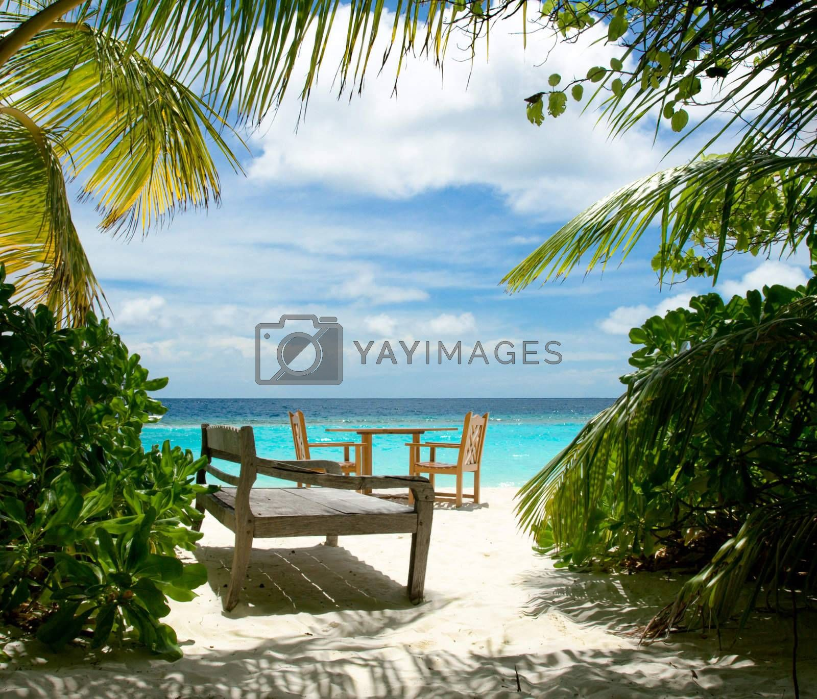 Free table for two and wooden sun bed on the tropical beach