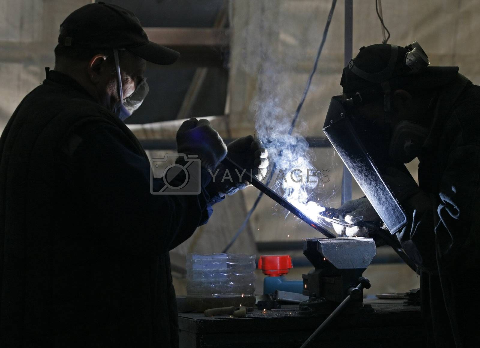 Workers welding metal and sparks spreading