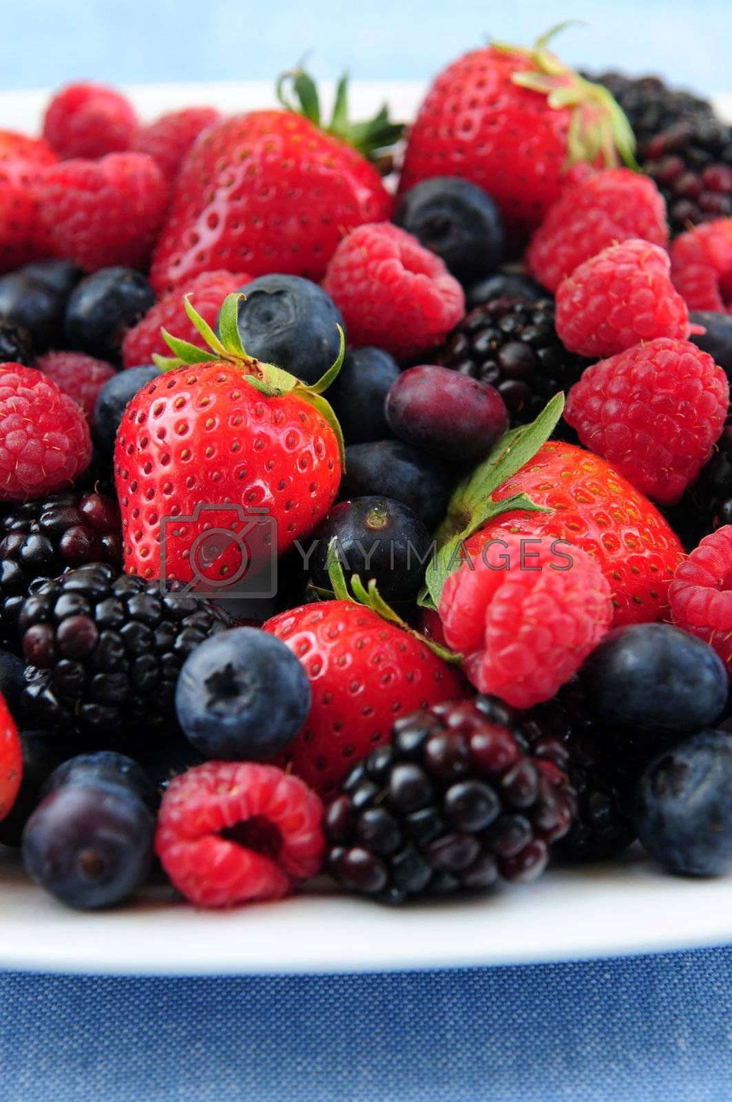 Assorted fresh berries on a plate close up
