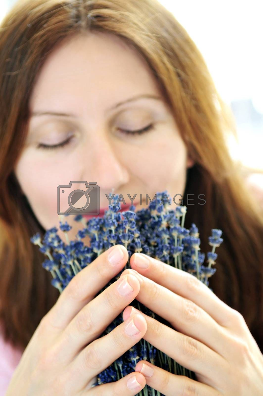 Mature woman smelling lavender flowers - focus on hands