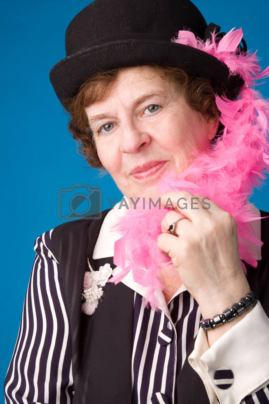 The cheerful elderly woman in black hat on a blue background.