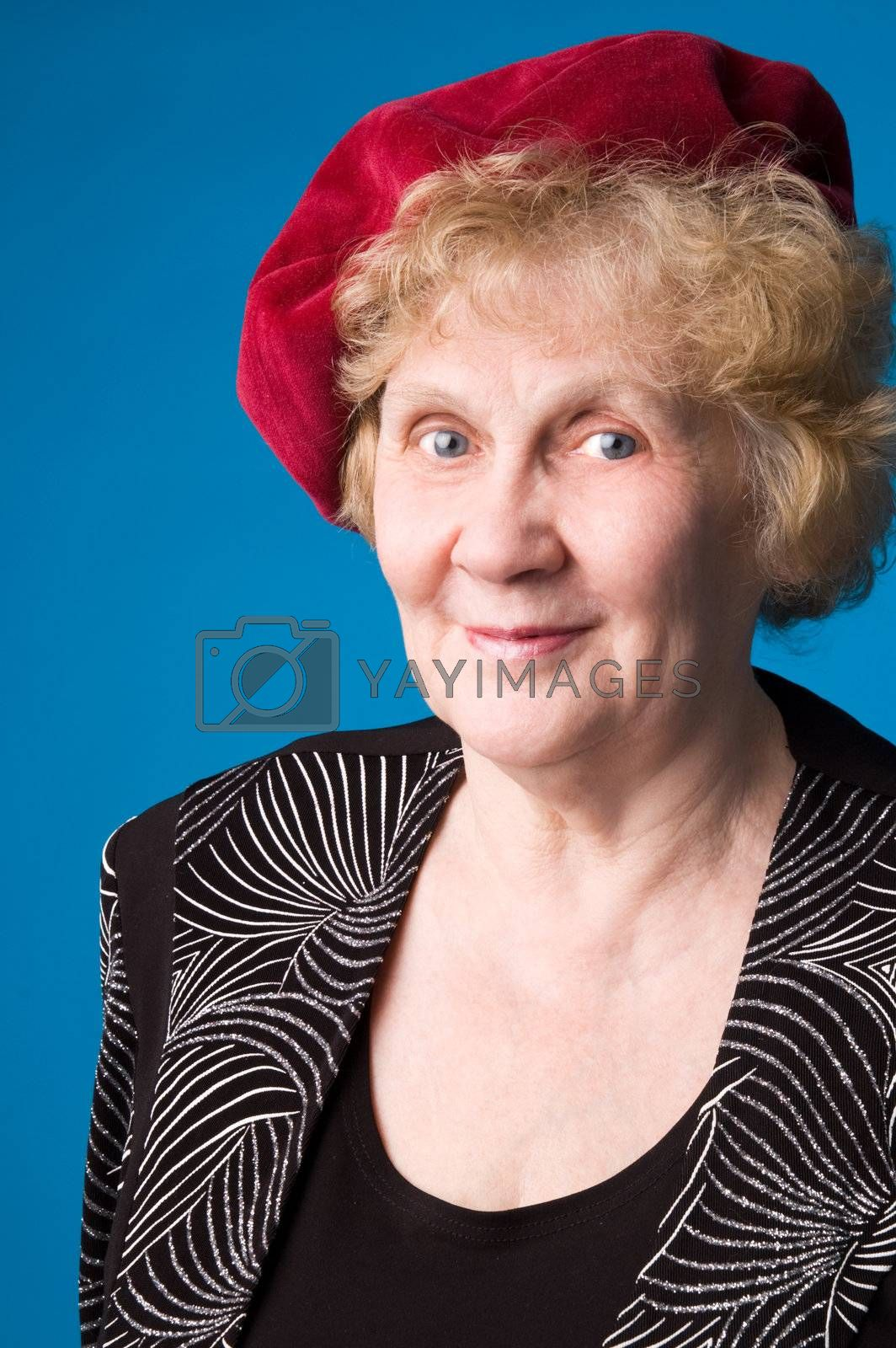 The cheerful elderly woman in red beret on a blue background.