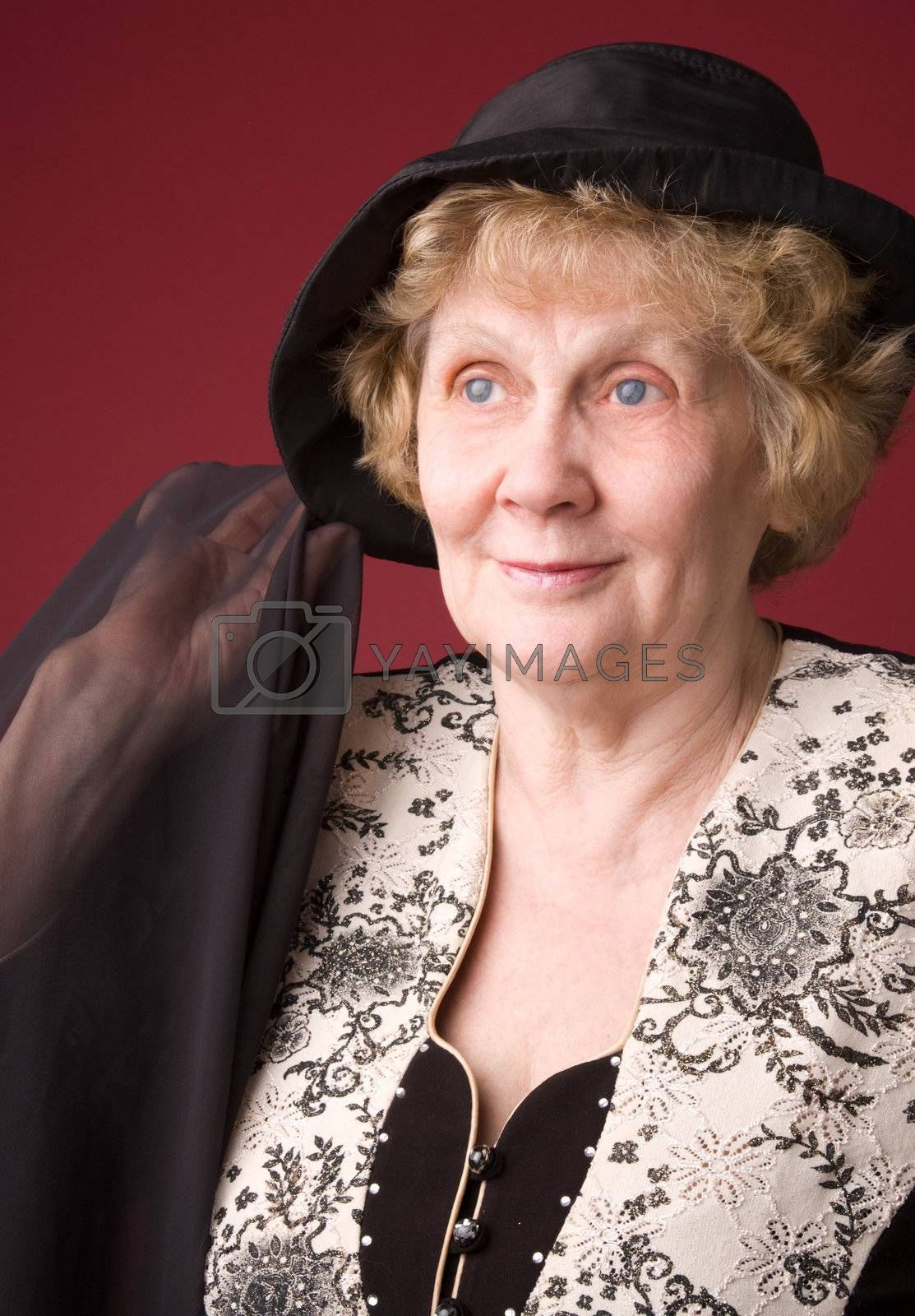 The cheerful elderly woman in hat on a red background.