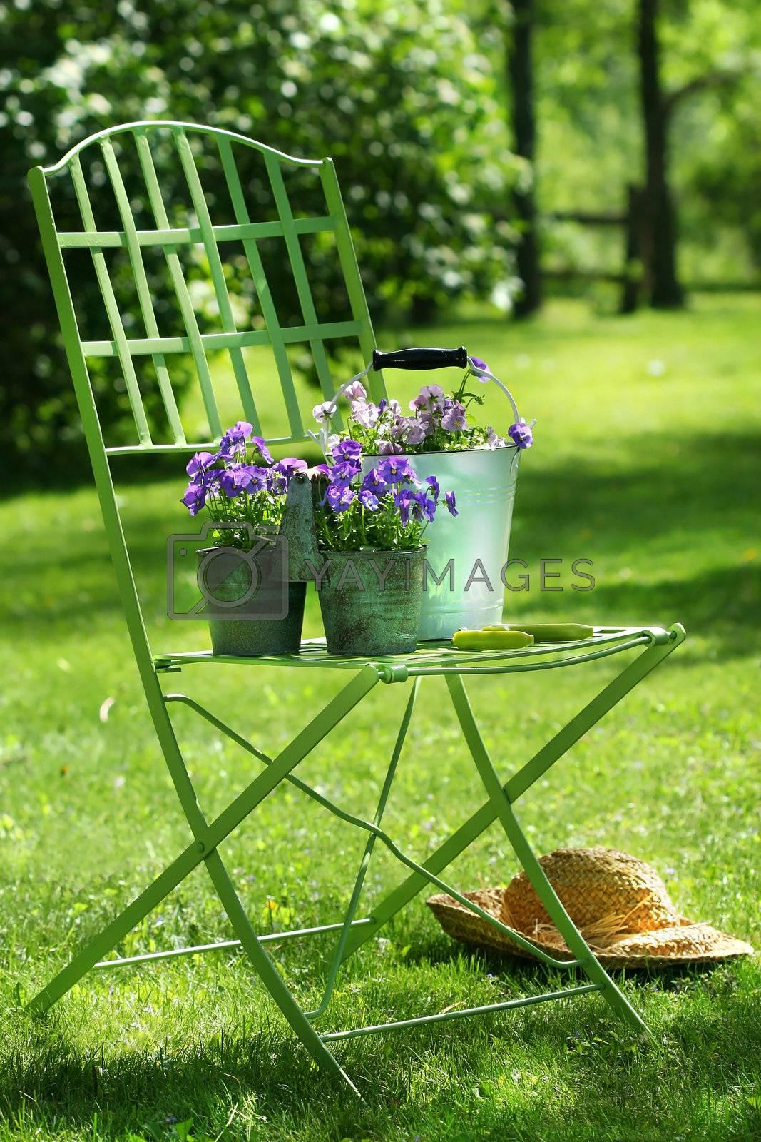 Green garden chair with straw hat