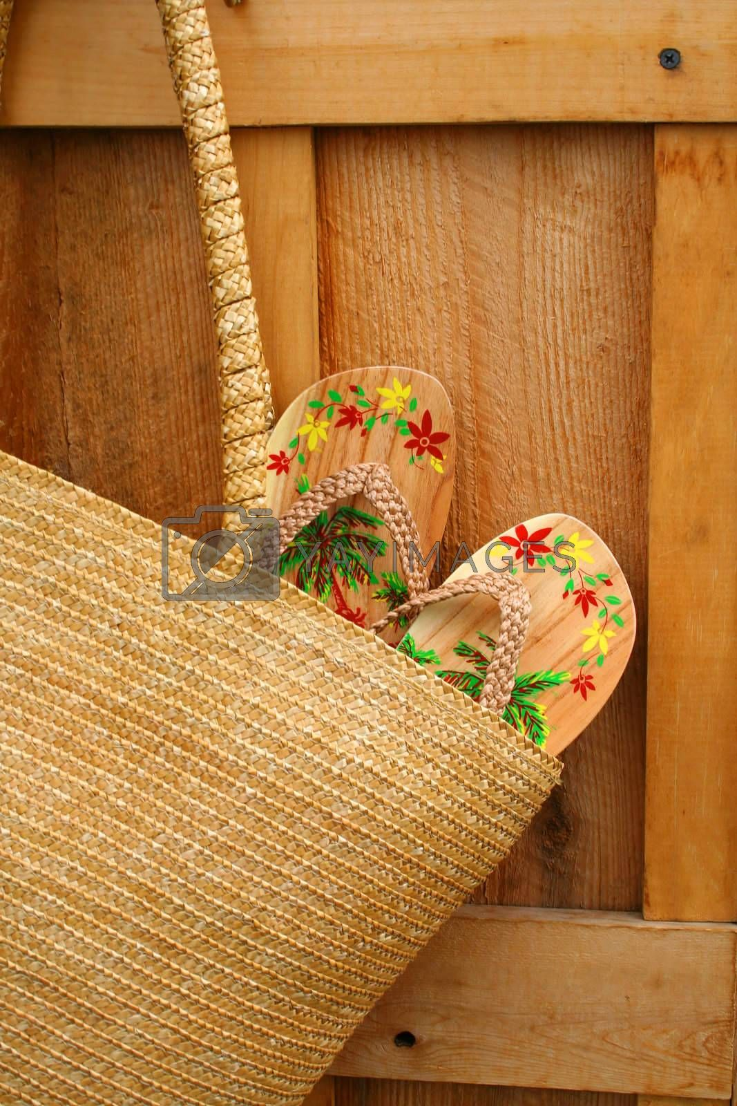 Pair of sandals hanging out of wicker purse/ closeup