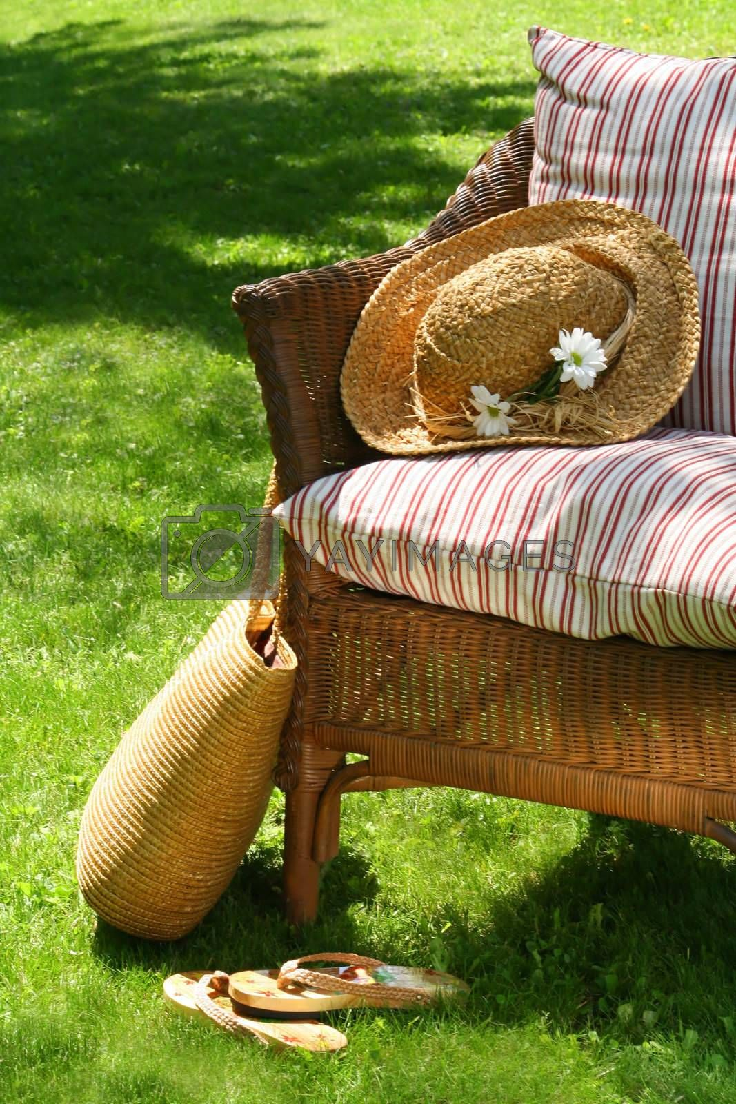 Grass lawn with a wicker chair waiting for someone to relax on a hot summer's day