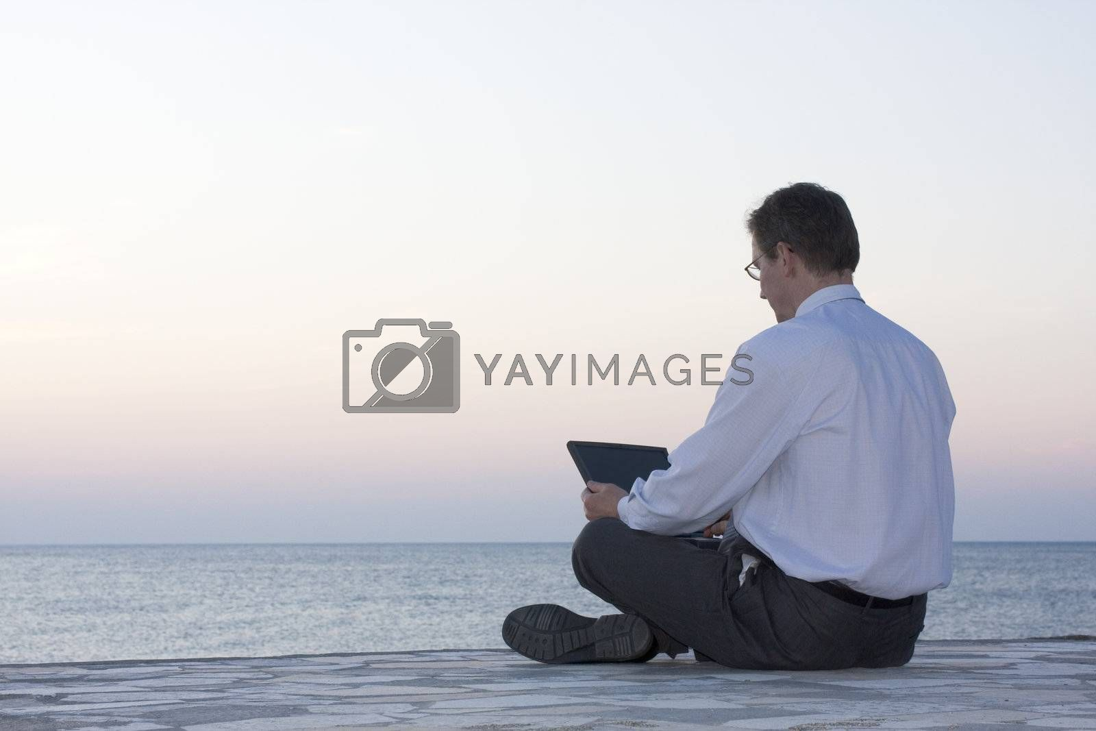 Businsessman working with laptop by the sea