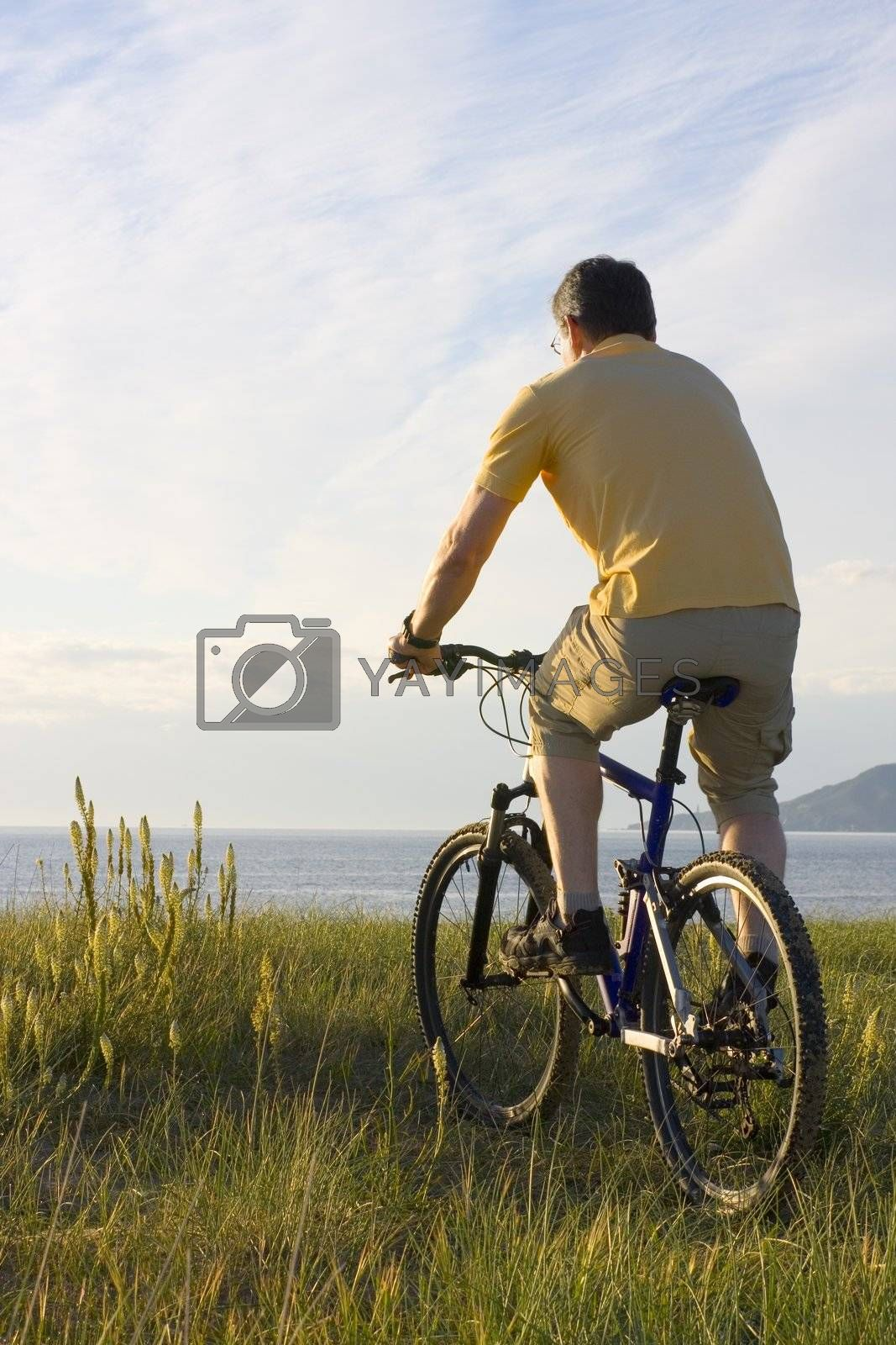 Man riding his bicycyle at the sea in the morning