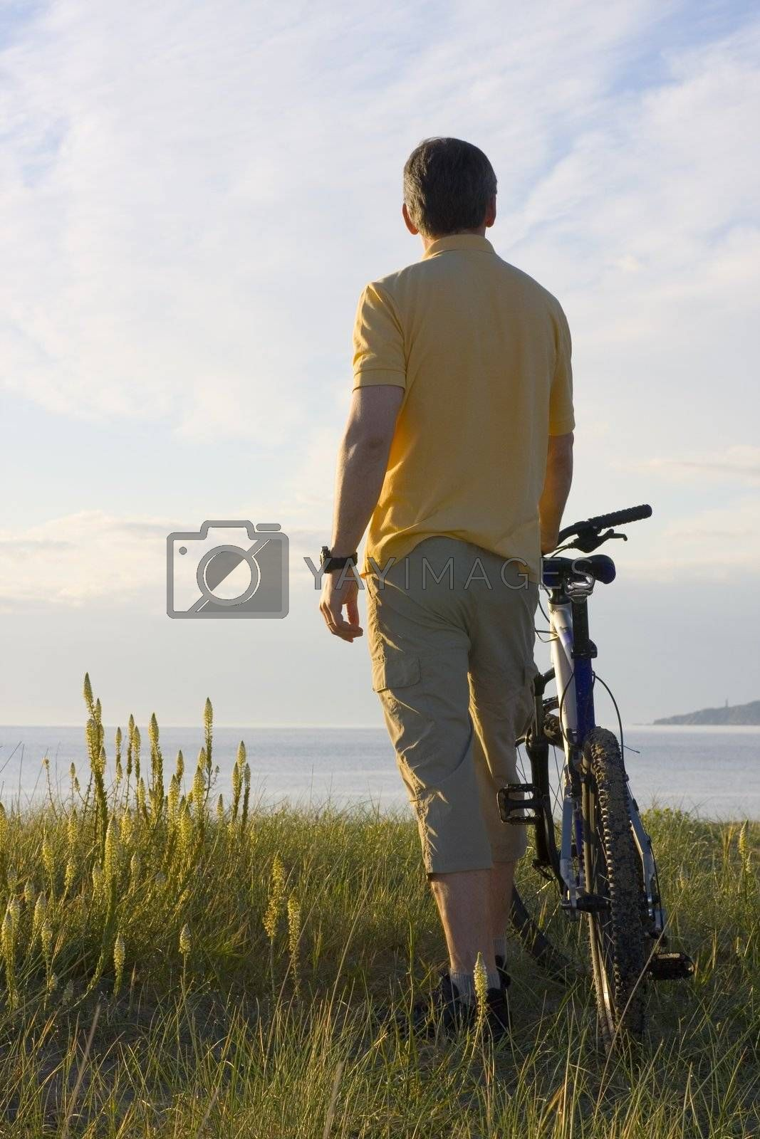 Man standing by his cycle at the sea