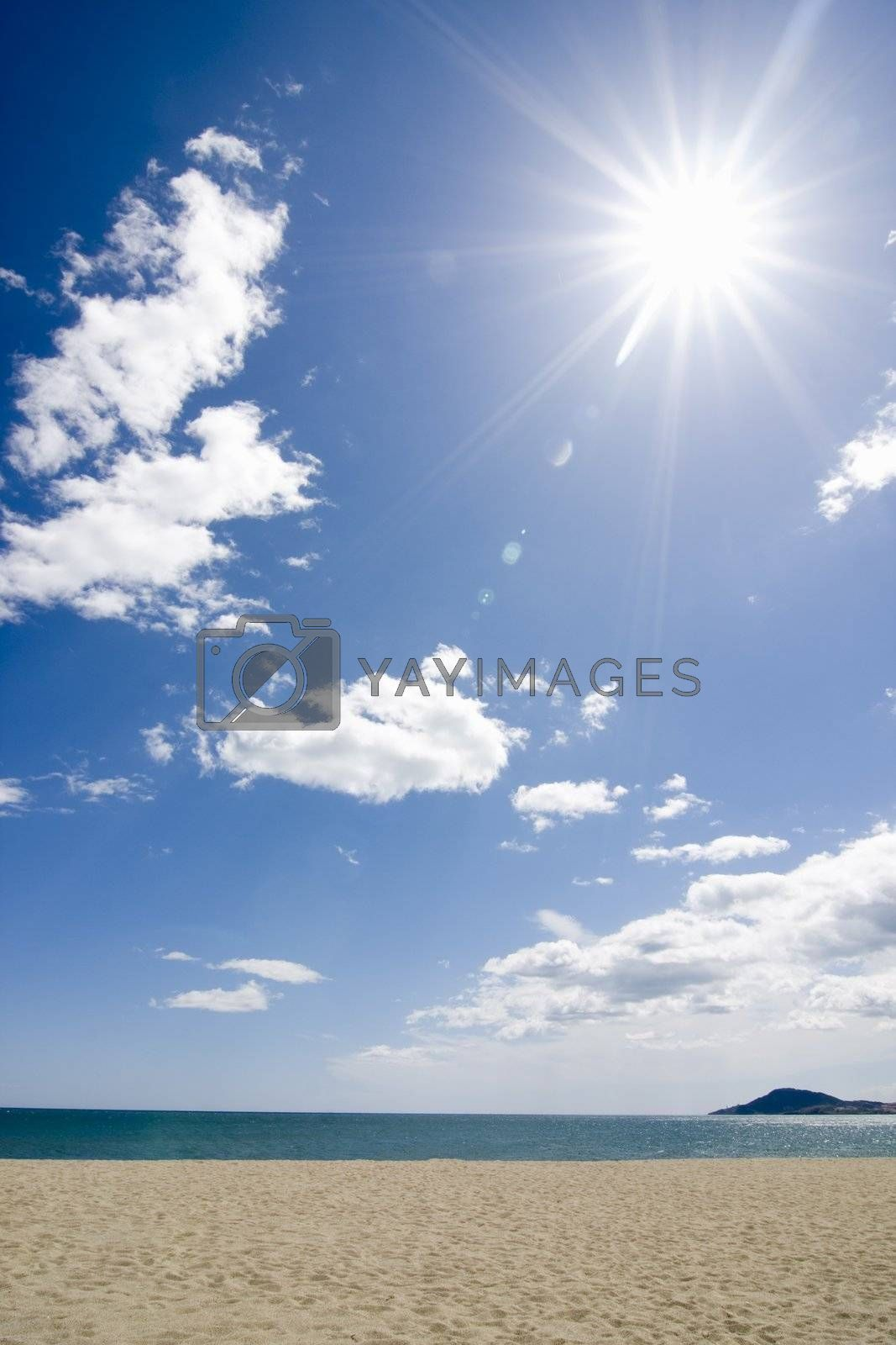 Sun shining on the beach with blue sky and clouds
