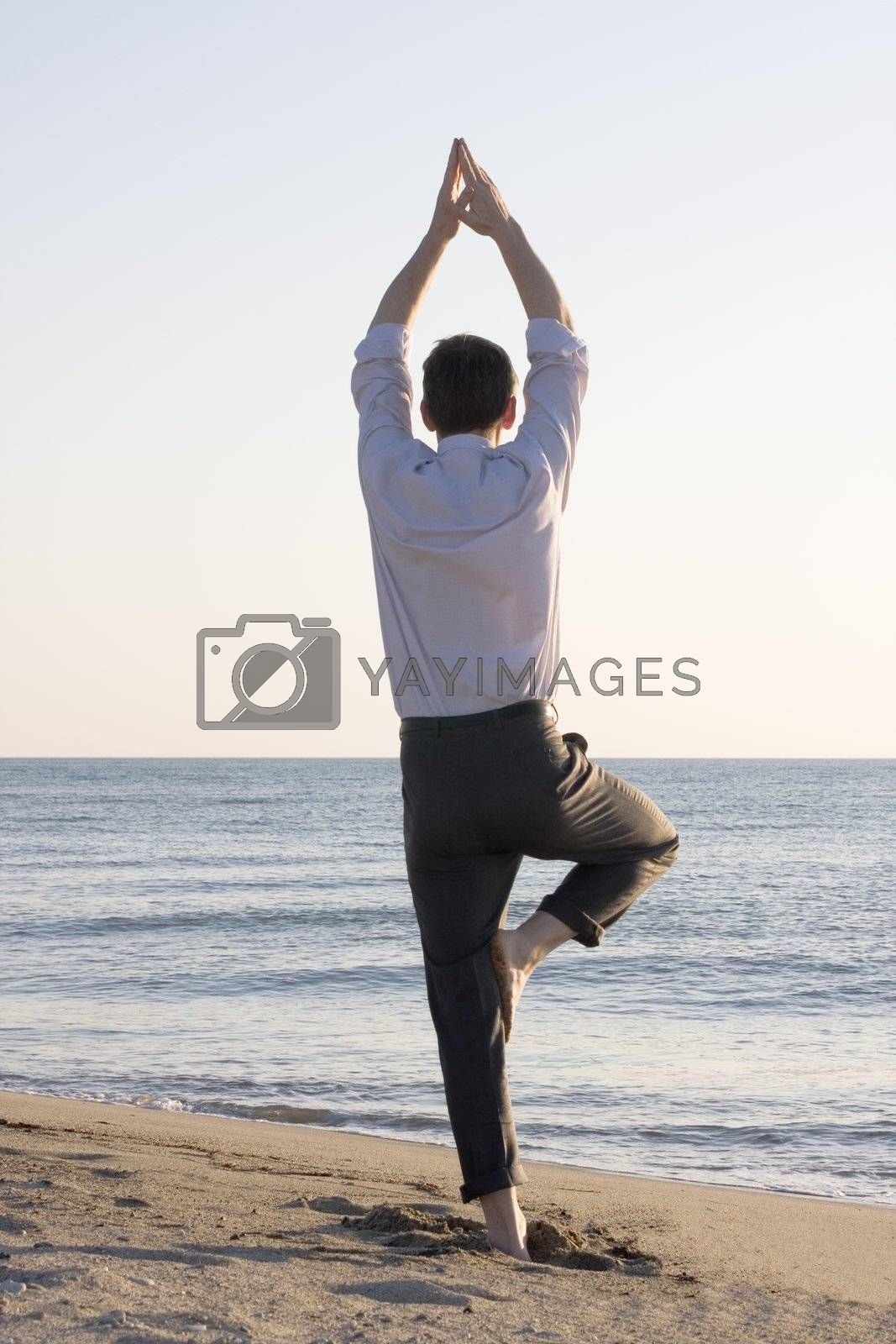Businessman doing yoga on the beach
